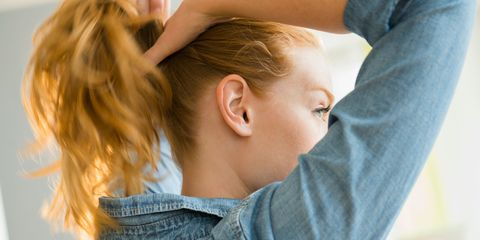 Young woman tying hair