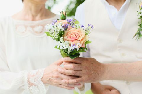 an elderly couple hold a bouquet of flowers at their wedding