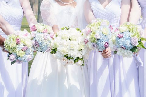 Bride stands with bridesmaids holding flowers