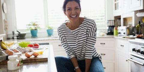 Woman smiling in kitchen next to counter of healthy food