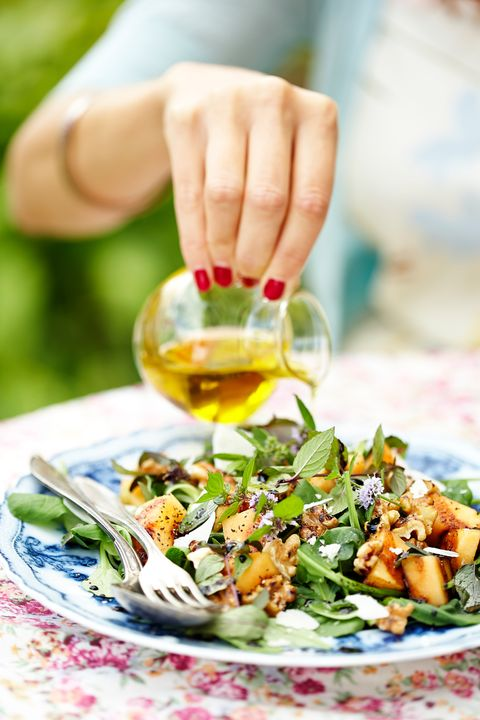 Woman pouring dressing on salad