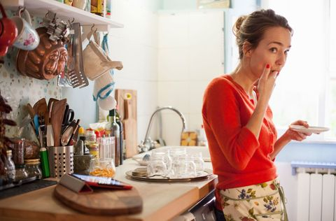Woman licks food off her finger while in the kitchen