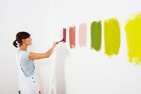 Woman paints lots of different colours onto a white wall