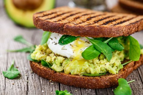 Avocado and egg between two pieces of toasted bread