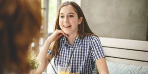 girl sitting at the restaurant with her meal and juice, smiling