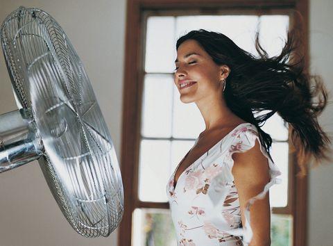 Woman standing in front of fan