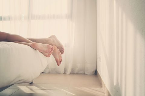 Couple dangle their legs over the edge of the bed