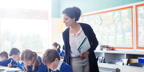 Teacher helps child in classroom