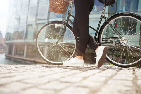 Woman stands holding bike on cobbled street