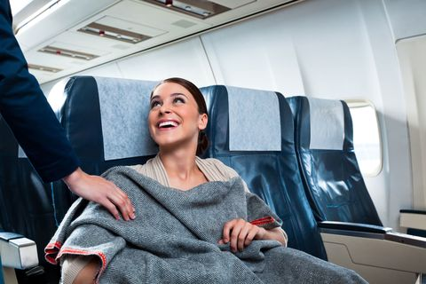 Woman wrapped in a blanket on a flight