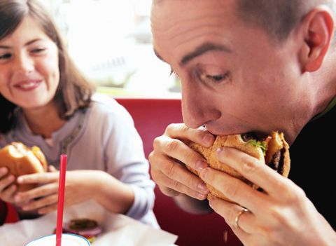 Dad and daughter eating burgers