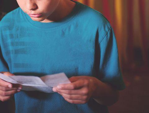Little boy reading letter