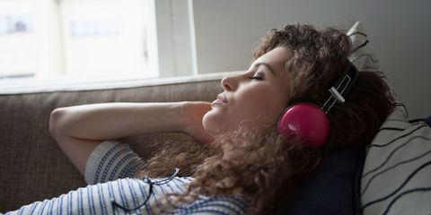 Woman wearing headphones asleep on sofa