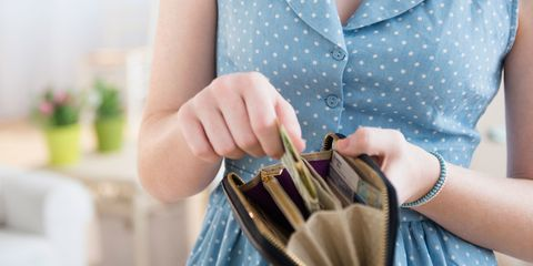 Woman putting money in purse