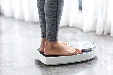 Woman stands on weighing scales