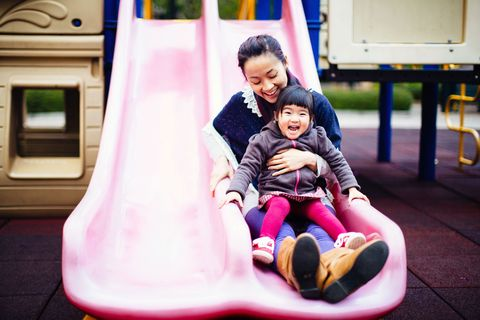 Parent and child go down slide