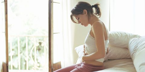 Woman sitting in bed holding her stomach