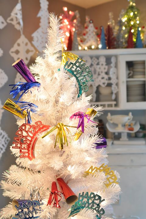 """<p>Strip your tree down to the needles and lights, and then adorn it with party poppers and streamers.&nbsp;It doesn't get easier than that!</p><p><em data-redactor-tag=""""em""""><a href=""""http://www.domesticfashionista.com/2011/12/new-years-eve-tree.html"""" target=""""_blank"""" data-tracking-id=""""recirc-text-link"""" data-href=""""http://www.domesticfashionista.com/2011/12/new-years-eve-tree.html"""">Get the tutorial from Domestic Fashionista »</a></em></p>"""