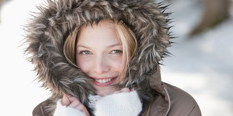 Woman wrapped up warm in winter fur hood coat snow