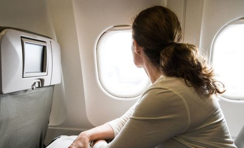 Woman staring out of plane window