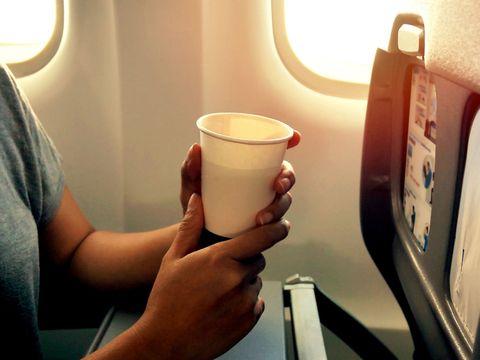 Woman drinking on plane