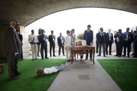 Prime Minister Justin Trudeau, wife Sophie Gregoire Trudeau, and children, Xavier, 10 and Ella-Grace, 9, sign a guest book as Hadrien, 3, plays on the ground during a visit to Rajghat Gard in New Delhi