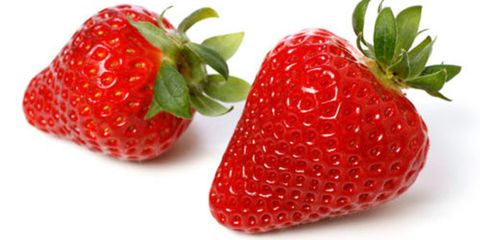 closeup of two ripe red strawberries on white background
