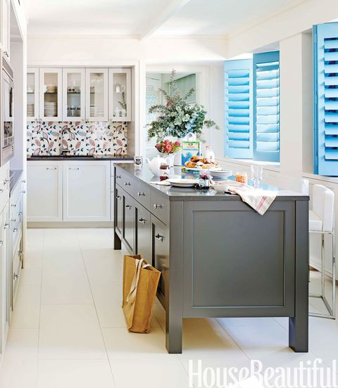 <p>Shutters painted in Benjamin Moore Aura in Old Blue Jeans bring a bright English country note into this urban kitchen. The island was designed to look like a piece of furniture and is painted in Benjamin Moore Aura in Iron Mountain. Counter stools by Calligaris.</p>