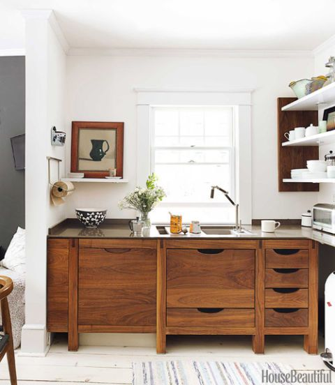 <p>Walls painted in Benjamin Moore Aura in Gardenia set off dark Bornholm cabinetry. In the eating area, a feature wall in Benjamin Moore Aura in Gray displays a changing selection of artwork.</p>