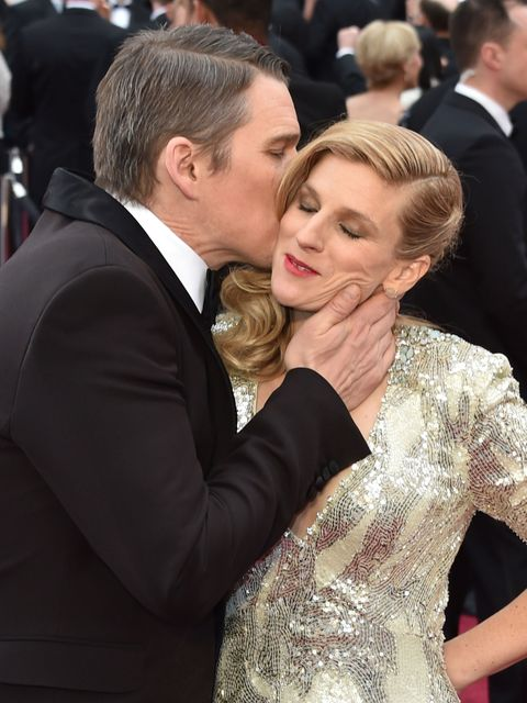 Nominee for Best Supporting Actor  Ethan Hawke (L) kisses his wife Ryan Hawke as they arrive on the red carpet for the 87th Oscars on February 22, 2015 in Hollywood, California. AFP PHOTO / MLADEN ANTONOV        (Photo credit should read MLADEN ANTONOV/AFP/Getty Images)