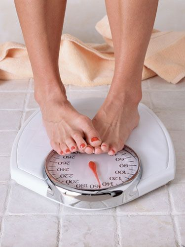 woman's feet standing on bathroom scale