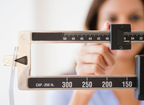 Woman measuring her weight on a scale