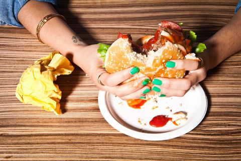 Woman with green nails eating burger