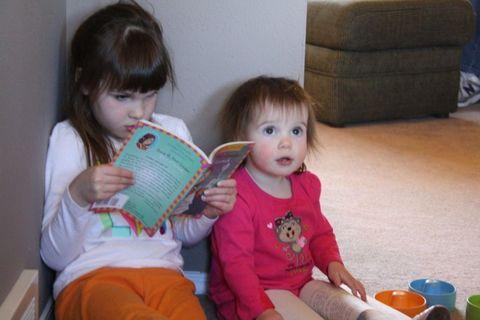 Child, Hand, Comfort, Baby & toddler clothing, Sitting, Sharing, Toddler, Reading, Lap, Brown hair,
