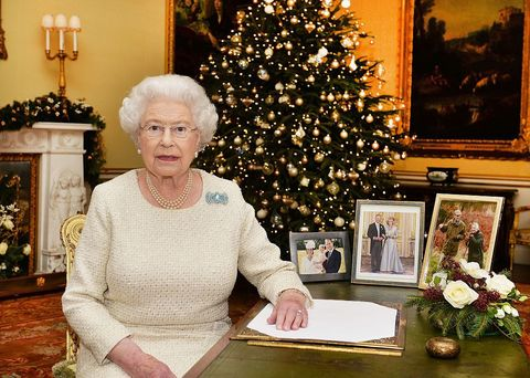 <p>The Queen is like every other mom and grandmother: Extremely proud of her family, as evident by the family photos on her desk. We also couldn't help but notice how her ensemble coordinates with the ivory flowers and tree ornaments.</p>