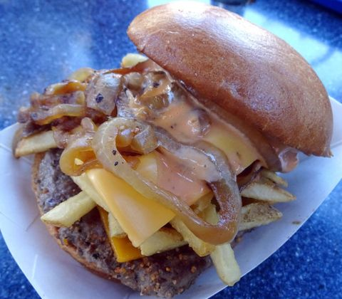 """<p>Sold at the Galactic Grill in Tomorrowland, be sure to order this <a href=""""http://www.delish.com/restaurants/videos/a51430/disney-world-best-burger/"""" target=""""_blank"""" data-tracking-id=""""recirc-text-link"""" data-unsp-sanitized=""""clean"""">burger</a> if you're looking to fill your stomach – and&nbsp;possibly clog your arteries. Just order the Galactic Style Burger topped with fries, bacon, cheese and grilled onions, then smother it&nbsp;with Thousand Island dressing and cheese. It's guaranteed to make you feel out of this world.</p>"""