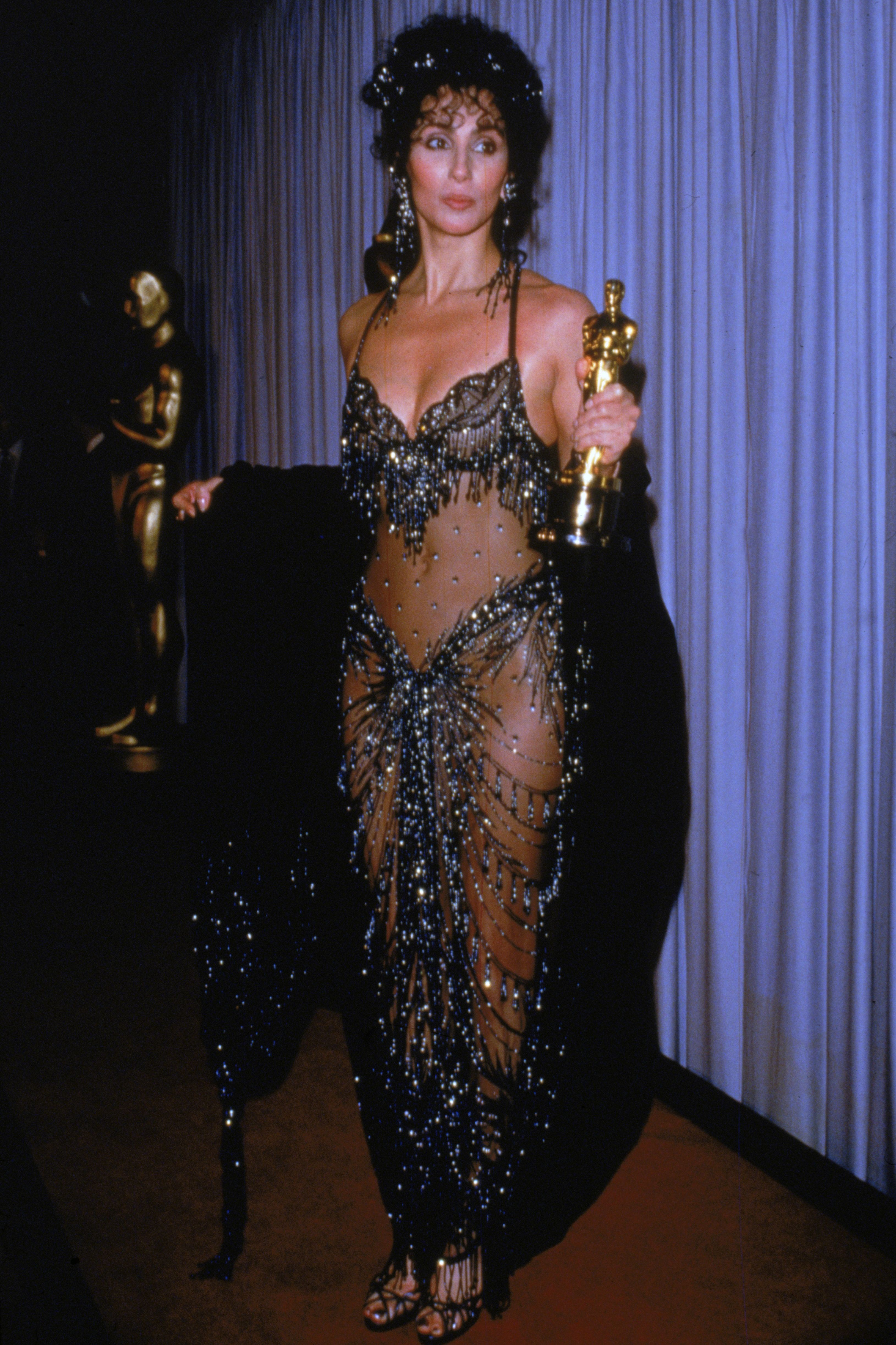 """<p>Cher picked up the Academy Award for Best Actress for her moving performance in <em data-verified=""""redactor"""" data-redactor-tag=""""em"""">Moonstruck</em><span class=""""redactor-invisible-space"""" data-verified=""""redactor"""" data-redactor-tag=""""span"""" data-redactor-class=""""redactor-invisible-space"""">, but it's</span>safe to say that the public was just as riveted by her choice of dress at the ceremony. A hybrid between a bra and a sarong,Cher's sheer Bob Mackie design exposed the entirety of her <a href=""""http://www.goodhousekeeping.com/health/diet-nutrition/a44341/what-cher-eats-in-a-day/"""" target=""""_blank"""" data-tracking-id=""""recirc-text-link"""">toned stomach and legs</a>, with a strategic clustering of rhinestones just below the navel.</p>"""