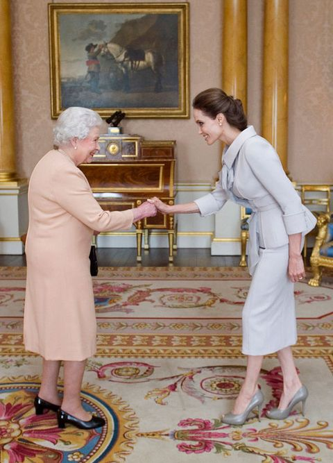 """<p>If you're a citizen of the United States, you can simply shake hands, but inGreat Britain, <a href=""""http://www.eonline.com/shows/the_royals/news/610777/8-things-you-should-never-do-when-meeting-the-royals"""" target=""""_blank"""" data-tracking-id=""""recirc-text-link"""">men and women must bow or curtsy</a>. When Angelina Jolie, who is a US citizen met the Queen, you see she did a little of all three, because it's better to be safe than sorry!<span class=""""redactor-invisible-space"""" data-verified=""""redactor"""" data-redactor-tag=""""span"""" data-redactor-class=""""redactor-invisible-space""""></span></p>"""