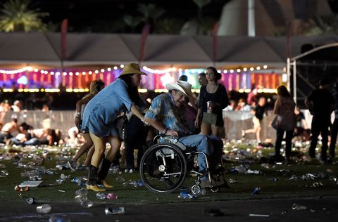 <p>A woman pushes a man in a wheelchair as concertgoers seek cover. </p>