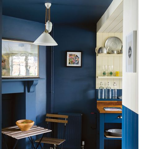 "<p>More than the walls were painted blue here—check out the ceiling and the fireplace. ""Using one color in a confined area makes it feel bigger,"" says Joa Studholme, author of Farrow &amp; Ball's book <em data-redactor-tag=""em"" data-verified=""redactor""><a href=""https://www.amazon.com/Farrow-Ball-How-Decorate/dp/1784720879"" target=""_blank"" data-tracking-id=""recirc-text-link"">How to Decorate</a></em>, who adds that if the mantel were white, it would dwarf the room. Another reason to go monochromatic? It helps mask not-so-pretty stuff like exposed pipes or a radiator (use a forgiving eggshell finish). The half-painted walls mark the transition into the kitchen and break up all that navy.</p><p><strong data-verified=""redactor"" data-redactor-tag=""strong"">RELATED: <a href=""http://www.redbookmag.com/home/decor/g4538/cheap-home-makeover/"" target=""_blank"" data-tracking-id=""recirc-text-link"">How to Do a Home Makeover Without Breaking the Bank</a></strong><br></p>"