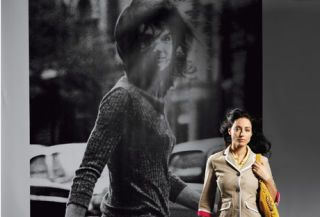 woman in jeans and blazer walking in front of jackie o poster