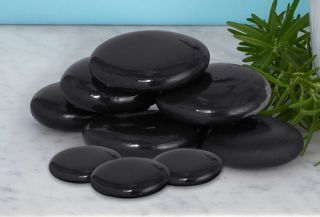 flat smooth dark round river rocks on marble counter with rosemary