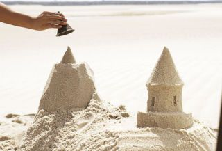 hand using a funnel to build a sandcastle tower