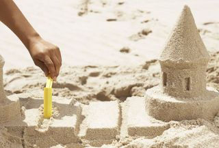Hand Using Yellow Tool To Drag Lines In Sand On Sandcastle