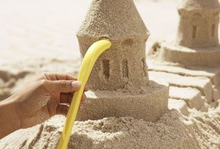 hand using shaping tool to add details to sand castle tower