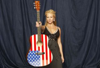 musician jewel holding a guitar painted with an american flag pattern