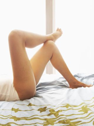 female legs crossed laying in bed