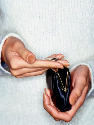 womans hands picking change out of a coin purse
