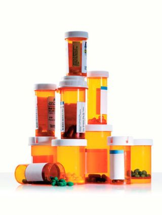 tower of prescription bottles filled with pills