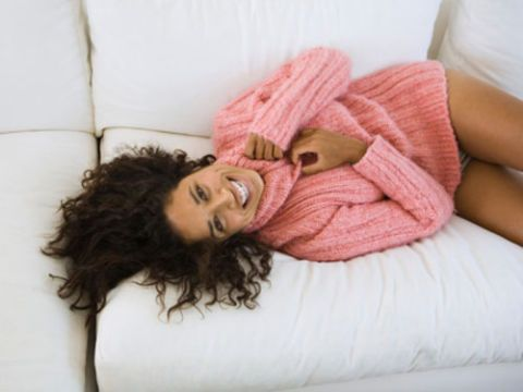 woman in fuzzy pink sweater and panties on white couch